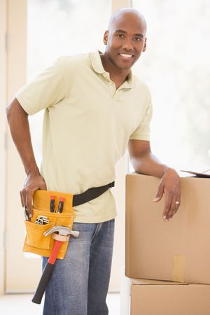 first time buyer: Man wearing tool belt standing by boxes in new home smiling