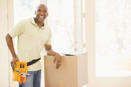 property ladder: Man wearing tool belt standing by boxes in new home smiling