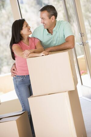 Couple with boxes in new home smiling photo