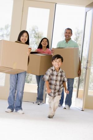asian home: Famiglia con caselle di nuovo in movimento in casa sorridente