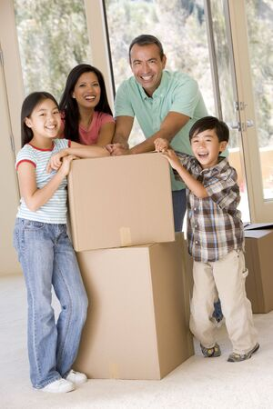 Family with boxes in new home smiling photo