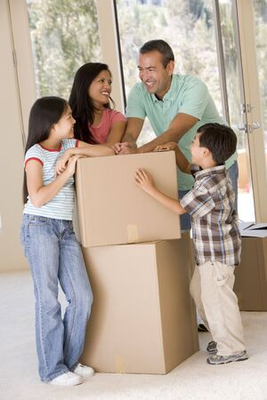 filipino: Family with boxes in new home smiling Stock Photo
