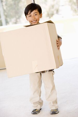 first time buyer: Young boy with box in new home smiling Stock Photo