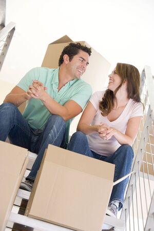 first time buyer: Couple sitting on staircase with boxes in new home smiling