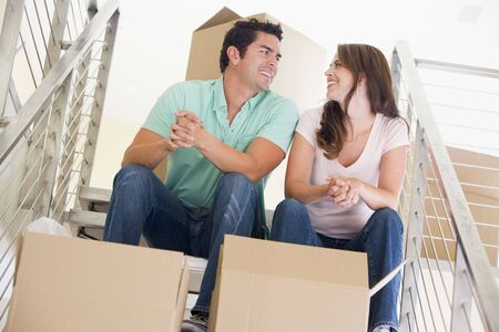 Couple sitting on staircase with boxes in new home smiling photo