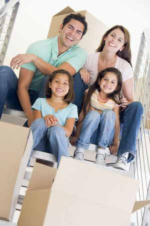 Family sitting on staircase with boxes in new home smiling photo