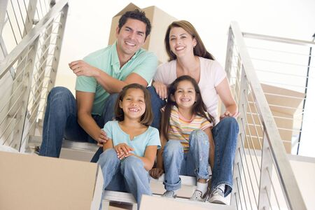 unpacking: Family sitting on staircase with boxes in new home smiling