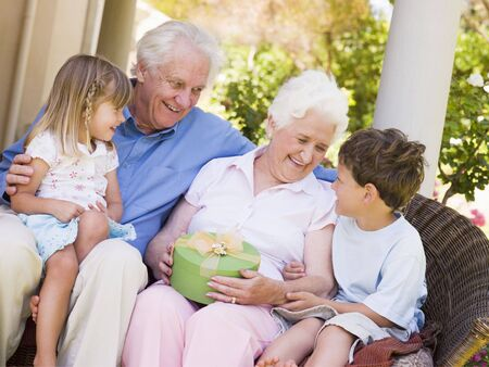 Grandparents with grandchildren on patio with gift smiling Stock Photo - 3488230
