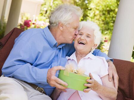 Husband giving wife gift on patio kissing her and smiling Stock Photo - 3488196