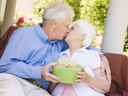 Husband giving wife gift on patio and kissing her Stock Photo - 3488226