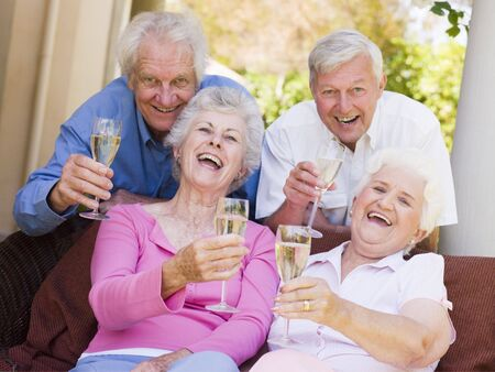Two couples on patio drinking champagne and smiling photo