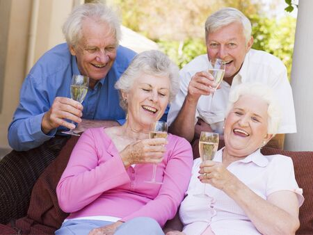 Two couples on patio drinking champagne and smiling Stock Photo - 3488235