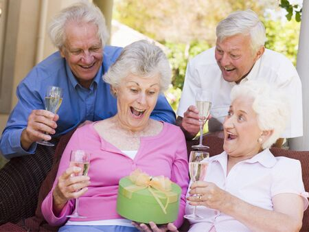 Two couples on patio with champagne and gift smiling photo