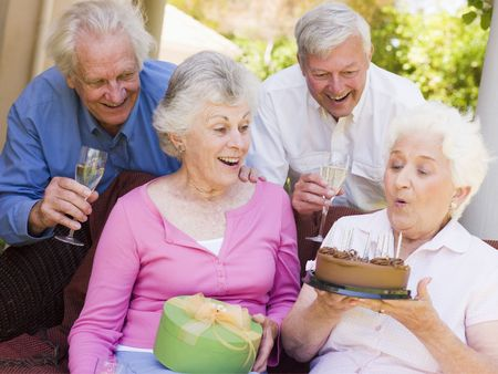 Two couples on patio with cake and gift smiling Stock Photo - 3488222
