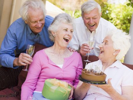 senior friends: Two couples on patio with cake and gift smiling