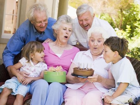 an old friend: Grandparents and grandchildren on patio with cake and gift smiling