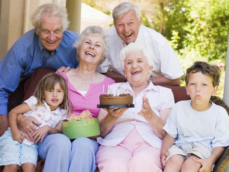 Grandparents and grandchildren on patio with cake and gift smiling photo