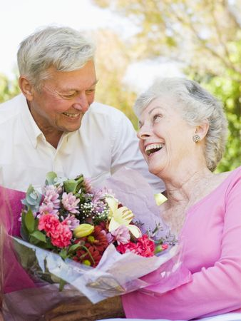 Husband giving wife flowers outdoors smiling photo