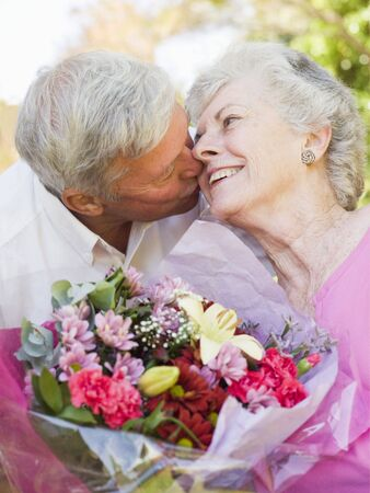 anniversary flower: Husband giving wife flowers outdoors kissing and smiling