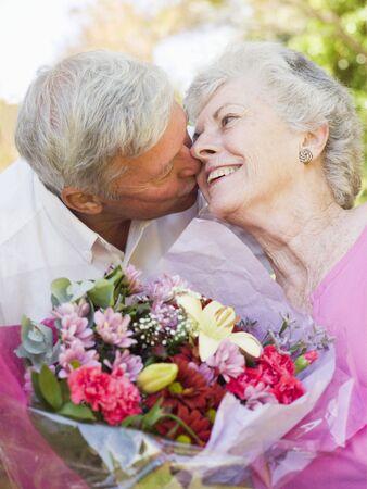 anniversario di matrimonio: Marito, moglie di fiori all'aperto baciando e sorridente