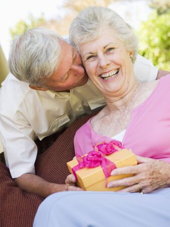 Husband giving wife gift on patio kissing her and smiling Stock Photo - 3488221