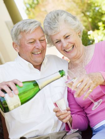 Couple on patio drinking champagne and smiling photo