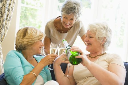 making fun: Three women in living room drinking champagne and smiling