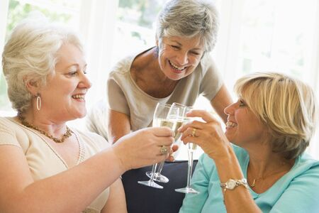 champagne flute: Three women in living room toasting champagne and smiling