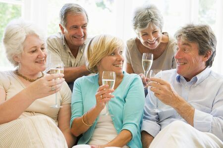 Five friends in living room drinking champagne and smiling Stock Photo - 3487510