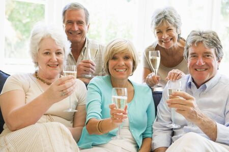 Five friends in living room drinking champagne and smiling photo