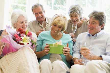 Five friends with champagne and gifts in living room smiling Stock Photo - 3488018