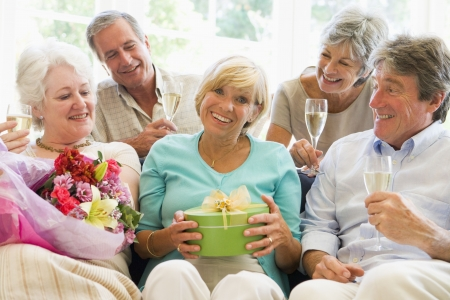 Five friends with champagne and gifts in living room smiling photo