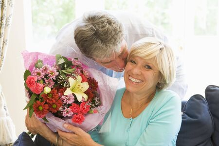 Husband giving wife flowers kissing and smiling Stock Photo - 3487373