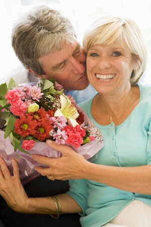 Husband giving wife flowers kissing and smiling photo