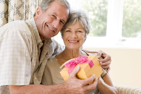 Husband giving wife gift in living room smiling Stock Photo - 3487214