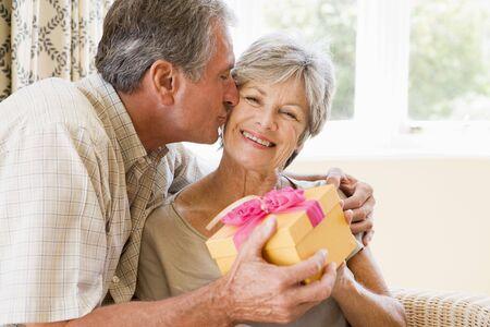 anniversario di matrimonio: Marito moglie dono che nel soggiorno e baciando il suo sorriso