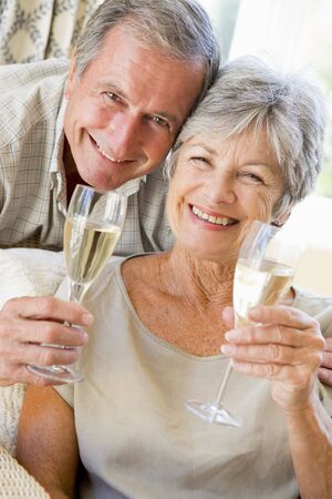 Couple in living room drinking champagne and smiling photo