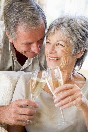 anniversario di matrimonio: Matura nel soggiorno toasting champagne e sorridente