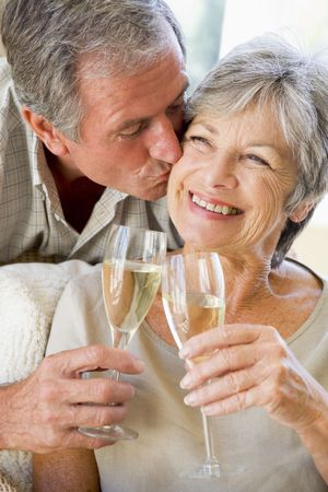 Couple in living room toasting champagne kissing and smiling photo