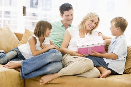 mom and dad: Family in living room with mother receiving gift and smiling Stock Photo