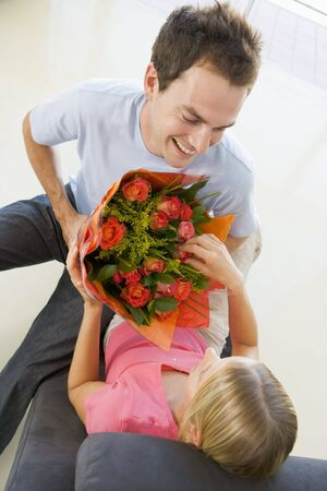 Husband giving wife flowers and smiling Stock Photo - 3487151