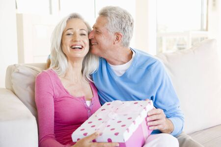 Husband giving wife gift in living room kissing her and smiling Stock Photo - 3486991