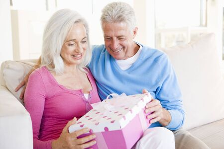 Husband giving wife gift in living room smiling Stock Photo - 3487389