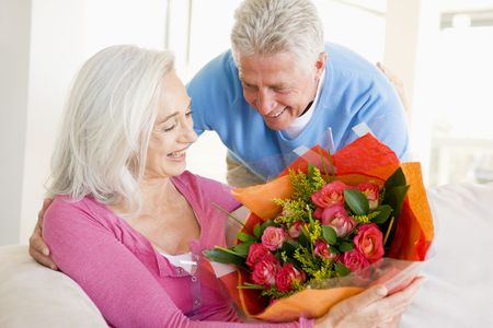 Husband giving wife flowers and smiling photo