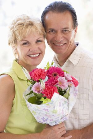jill: Husband and wife holding flowers and smiling Stock Photo
