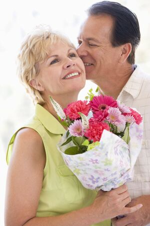 Husband and wife holding flowers kissing and smiling photo