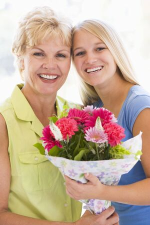 Granddaughter and grandmother holding flowers and smiling photo