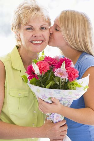jill: Granddaughter kissing grandmother on cheek holding flowers and smiling