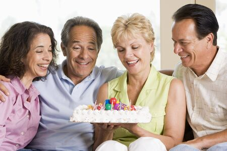 Two couples in living room with cake smiling Stock Photo - 3488182