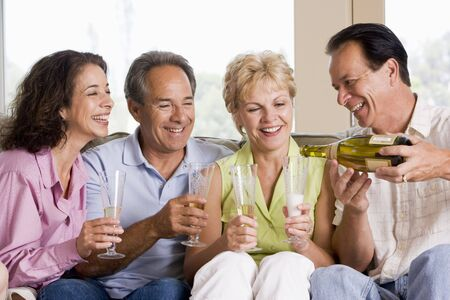 Two couples in living room drinking champagne and smiling Stock Photo - 3487942